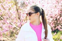 Schöne junge Jugendliche, die auf Frühlingshintergrund aufwirft Stockfoto