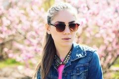 Schöne junge Jugendliche, die auf Frühlingshintergrund aufwirft Stockfotografie