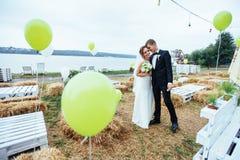 Schöne junge küssende Hochzeitspaare, blonde Braut mit flowe Stockfotos