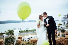 Schöne junge küssende Hochzeitspaare, blonde Braut mit flowe Lizenzfreie Stockbilder