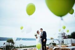 Schöne junge küssende Hochzeitspaare, blonde Braut mit flowe Stockfoto