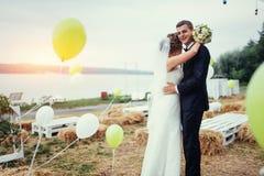 Schöne junge küssende Hochzeitspaare, blonde Braut mit flowe Lizenzfreies Stockfoto