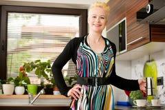 Schöne junge kaukasische blonde Frau, die herein Espressokaffee kocht Lizenzfreie Stockfotos