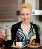 Schöne junge kaukasische blonde Frau, die herein Espressokaffee kocht Stockfotos