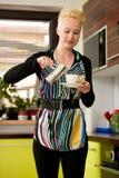 Schöne junge kaukasische blonde Frau, die herein Espressokaffee kocht Stockfotografie