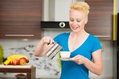 Schöne junge kaukasische blonde Frau, die herein Espressokaffee kocht Stockbilder
