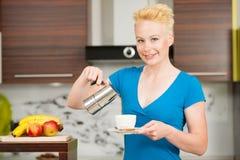 Schöne junge kaukasische blonde Frau, die herein Espressokaffee kocht Lizenzfreie Stockbilder