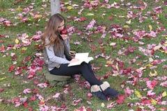 Schöne junge kaukasische Blondine, die einen Apfel, ein Buch lesend isst Lizenzfreies Stockfoto