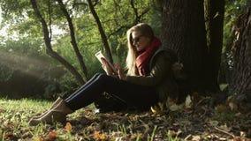 Schöne junge kaukasische Frauen, die Tablette im Park verwenden stock video