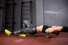 Schöne junge kaukasische Frauensportlerin benutzt einen Schaumrolle Massager für Entspannung und dehnt Muskeln und Rückenschmerze stockbilder
