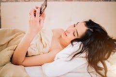 Schöne junge lächelnde brunette Frau, die Telefon in ihrem Schlafzimmer verwendet stockbilder