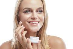 Schöne junge lächelnde Frau beim Addieren der Gesichtscreme Lizenzfreie Stockfotografie