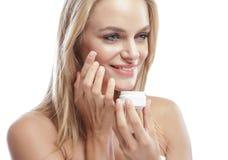 Schöne junge lächelnde Frau beim Addieren der Gesichtscreme Stockfotografie