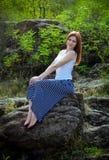 Schöne junge lächelnde Frau, die auf einer Steinklippe in einem Wald sitzt Lizenzfreie Stockfotografie