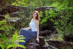 Schöne junge lächelnde Frau, die auf einer Steinklippe in einem Wald sitzt Stockfoto