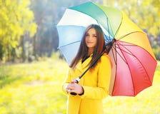 Schöne junge lächelnde Frau, die einen gelben Mantel mit Regenschirm trägt stockfoto
