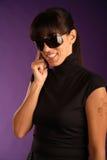 Schöne junge lächelnde Frau, die am Telefon spricht Stockfotografie