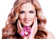 Schöne junge lächelnde Frau mit Blume nahe Gesicht Lizenzfreie Stockfotos
