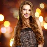 Schöne junge lächelnde Frau mit den langen Haaren, die Kamera betrachten Stockbild