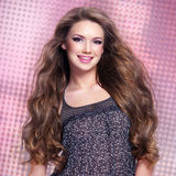 Schöne junge lächelnde Frau mit den langen Haaren, die Kamera betrachten Stockfotos