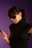 Schöne junge lächelnde Frau mit Mobiltelefon Lizenzfreie Stockbilder