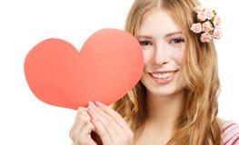 Schöne junge lächelnde Frau mit rotem Papiervalentinsgrußherzen Stockfotografie