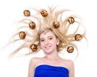 Schöne junge lächelnde Frau mit Weihnachtsdekorationen gegen lokalisiertes Weiß Lizenzfreie Stockbilder