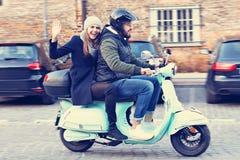 Schöne junge lächelnde Paare beim Reiten des Rollers in der Stadt im Herbst lizenzfreie stockfotos