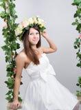 Schöne junge langbeinige Blondine in einem wenigen weißen Kleid auf einem Schwingen, hölzernes Schwingen verschob von einem Seilh Lizenzfreie Stockfotos