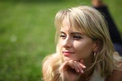 Schöne junge langhaarige blonde Aufstellung für die Kamera, die auf Gras liegt Stockbilder