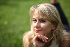 Schöne junge langhaarige blonde Aufstellung für die Kamera, die auf Gras liegt Lizenzfreie Stockfotos