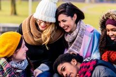 Schöne junge Leute, die zusammen im Park sitzen Lizenzfreies Stockbild
