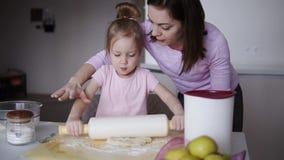 Schöne junge liebevolle Mutter, die ihren Bereitstellungsteig der netten kleinen Tochter mit einem Nudelholz beim Kochen unterri stock video
