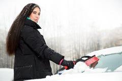 Schöne junge lustige Frau, die Schnee von ihrem Auto entfernt Stockfotografie