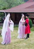 Schöne junge Mädchen und ein Junge werden an einem Handy in den traditionellen Circassian Kostümen am Festival von Käse Anzeige f lizenzfreie stockfotografie