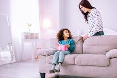 Schöne junge Mama, die nahe ihrer Tochter sitzt stockbilder