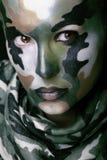 Schöne junge Modefrau mit Militärartkleidung und Gesicht malen Make-up Stockbild