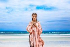 Schöne junge moderne Frau, die durch die Uferzone geht lizenzfreies stockbild