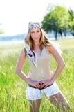 Schöne junge moderne Frau, die im hohen Gras steht Stockfoto