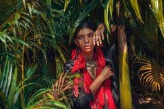 Schöne junge moderne Frau mit bilden und stilvolle boho Zusätze, die auf natürlichem tropischem Hintergrund aufwerfen stockfotografie