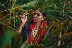 Schöne junge moderne Frau mit bilden und stilvolle boho Zusätze, die auf natürlichem tropischem Hintergrund aufwerfen stockbild