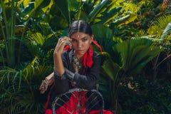 Schöne junge moderne Frau mit bilden und stilvolle boho Zusätze, die auf natürlichem tropischem Hintergrund aufwerfen lizenzfreie stockfotos