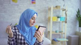 Schöne junge moslemische Frau macht Make-up, sich interessiert für Haut, Blicke im Spiegel stock video