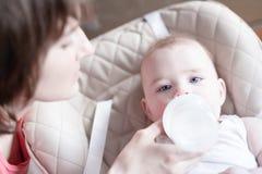 Schöne junge Mutter, die ihr Baby von der Flasche einzieht stockbild