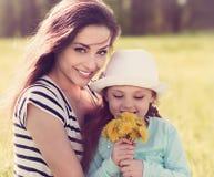 Schöne junge Mutter, die ihre nette Tochter mit gelbem b umfasst Lizenzfreies Stockfoto