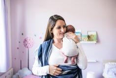 Schöne junge Mutter, die ihren Sohn in Riemen einwickelt stockbild