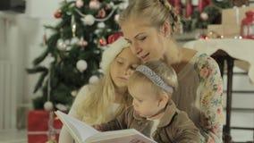 Schöne junge Mutter, die mit zwei entzückend sitzt stock video footage