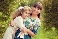 Schöne junge Mutter in einem Blumenkleid und in einer Tochter jugendlich 10 YE Stockbilder