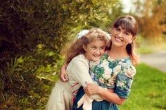 Schöne junge Mutter in einem Blumenkleid und in einer Tochter jugendlich 10 YE Lizenzfreies Stockfoto