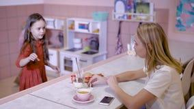 Schöne junge Mutter in einem Café Kinder im Tummelplatz, die Frau passt sie auf und trinkt stock video footage